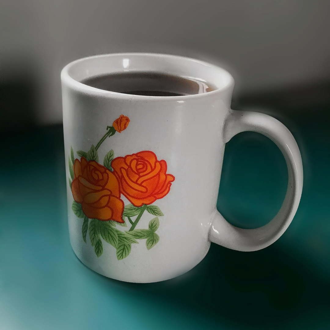 Image of white mug filled with black coffee. Mug has image of two red roses with green stems on it and sits on a teal surface against a grey background.